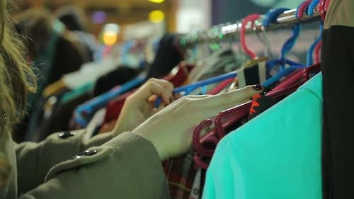 Female Customer Looking at Clothing Exhibition Organized by Local Manufacturers