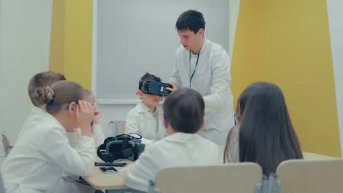 Little Boy in Virtual Reality Headset Standing in Classroom and Looking