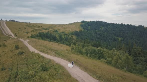 Thumbnail for The Groom Runs with Bride on a Mountain Hills. Aerial Drone Shot