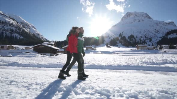 Thumbnail for A man and woman couple walking in the snow at a ski resort in the snow at the mountains