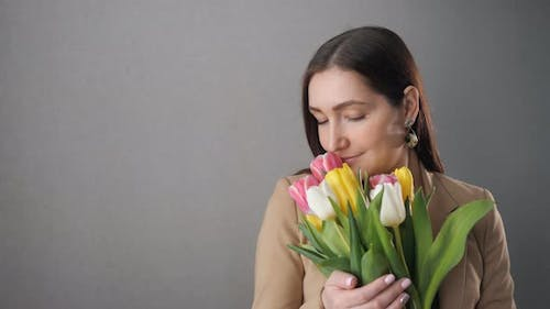 Beautiful Girl with a Bouquet of Tulips Enjoy and Looking Out the Window