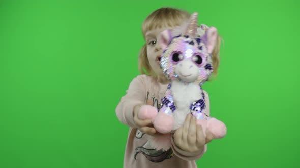Thumbnail for Positive Girl in Sweatshirt Dancing with Unicorn Toy