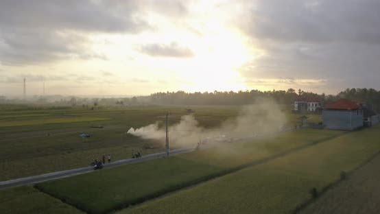 Aerial drone view of farming fields and a road with burning smoke at sunset.