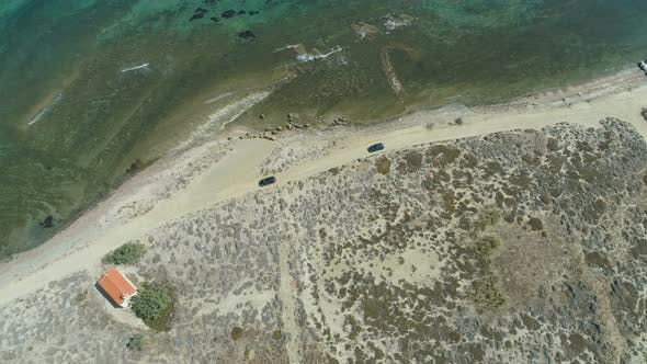 Drone Following Cars Driving Slow at Rocky Beach Coastal Road in Lemnos, Greece