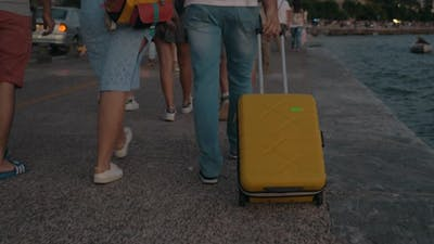 People Taking Travel Bag and Walking in the Crowd