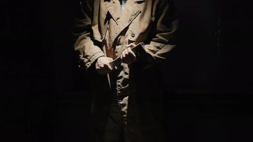 Man Murderer in a Cloak in a Dark Room with an Ax