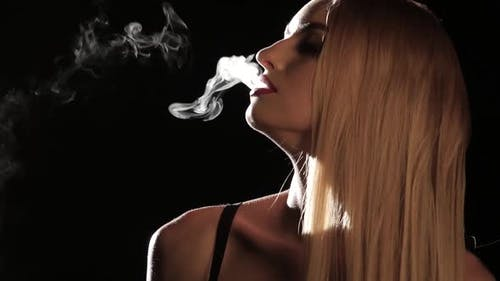 Girl Smokes an Electronic Cigarette in an Empty Room. Black Background