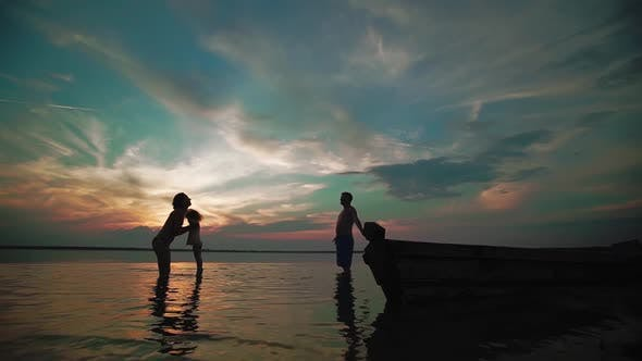Slow Motion. A Man A Man and Woman with a Child Play in Water on a Lake at Sunset