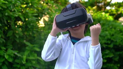 Asian Child With Virtual Reality Headset Touching Outdoors