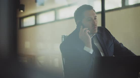 Thumbnail for A businessman having a serious and stressful conversation over the phone while working at the office