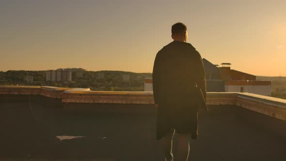 Thumbnail for The Camera Follows a Man Walking Across a Rooftop at Sunset with a Laptop and a Bottle