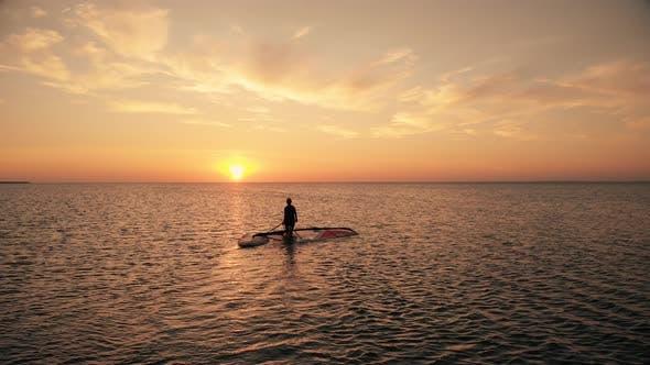 Silhouette of Woman Walking with Surfboard Along Calm Ocean