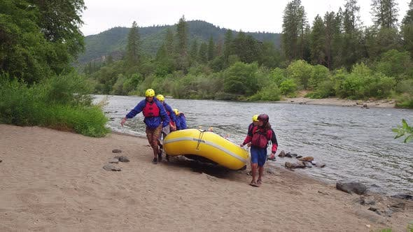Thumbnail for Group of people white water rafting carry raft together