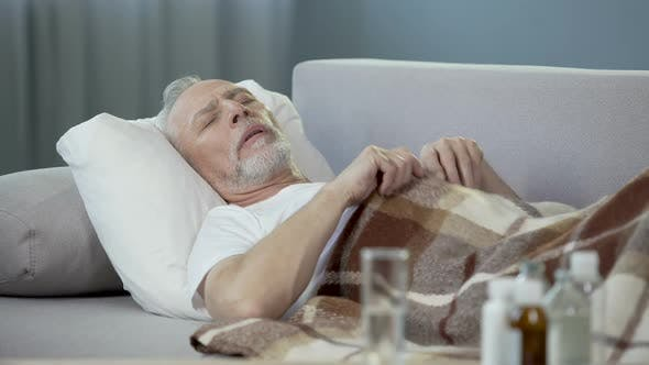 Thumbnail for Senior Male Sleeping on Couch, Suffering from High Temperature