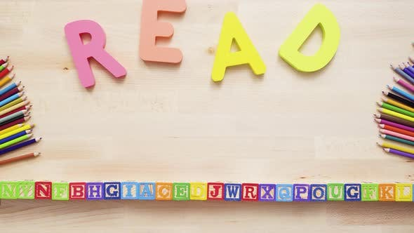 Thumbnail for Word READ from multicolor wooden letters on wooden table.