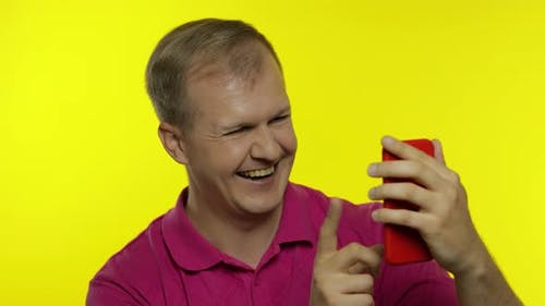 Young Man Posing in Pink T-shirt. Handsome Guy Using Mobile Phone, Watching Funny Videos Online