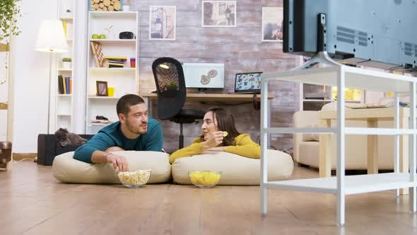Thumbnail for Couple Talking with Each Other Watching Tv Sitting on the Pillows for the Floor