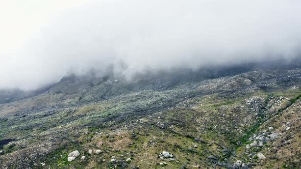 Aerial Shot of the Lush Mountains and Fog Covering the Top Area of Frame