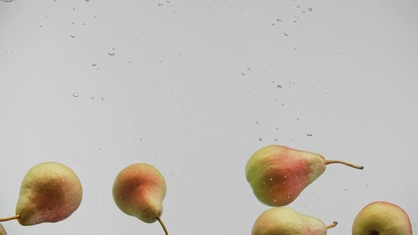 Cover Image for Yummy Fruits Red and Yellow Pears Falling Into Water with Splash and Air Bubbles White Background