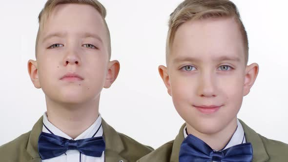 Thumbnail for Blond Blue-Eyed Identical Twins Posing Together on White