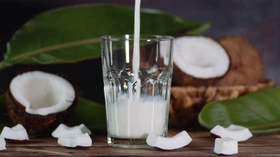 Coconut Milk Pouring Into a Glass. On a Dark Background.