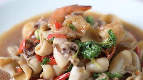 Squid and shrimp fried basil on a white plate