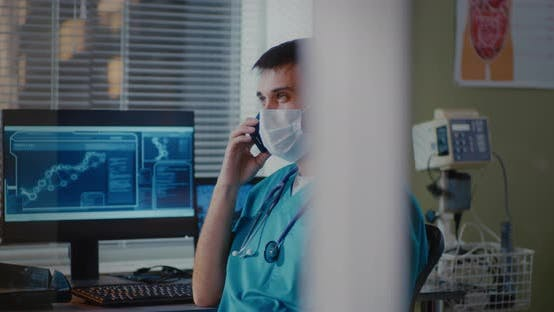 Doctor in Mask Talking on Smartphone Near Computer