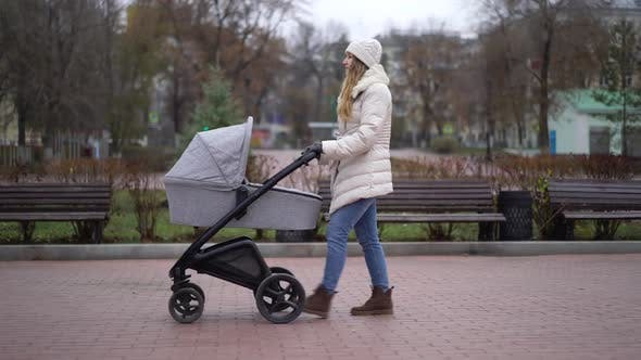 Thumbnail for Young Mother Walking with a Child in Pram. Autumn Season