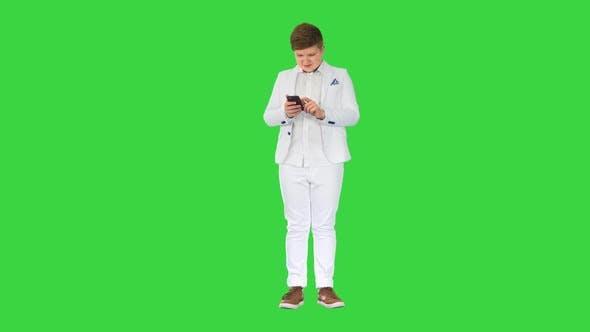 Junge Teenager im Business-Anzug mit Handy auf einem Greenscreen Chroma Key