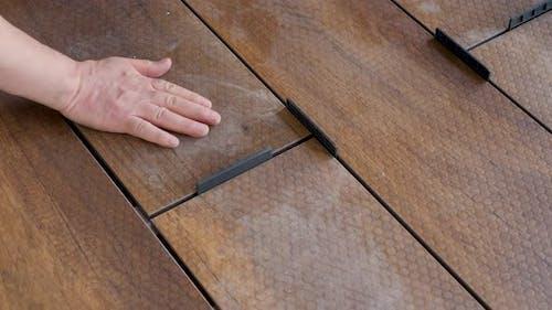 Zimmerer legt den Abstand der Deckbretter auf dem Boden fest Holzplatte