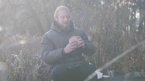 Thumbnail for Porträt von zuversichtlich kaukasischen Mann sitzt im Herbstwald und Essen Hot-Dog. Schöner Mann