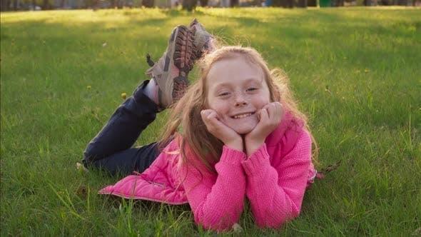 Thumbnail for Joyful Carefree Little Girl Lying on Grass and Smiling in Summer Park