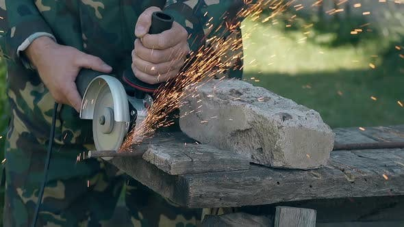 Thumbnail for Craftsman Cuts Metal Rod with Modern Instrument in Yard