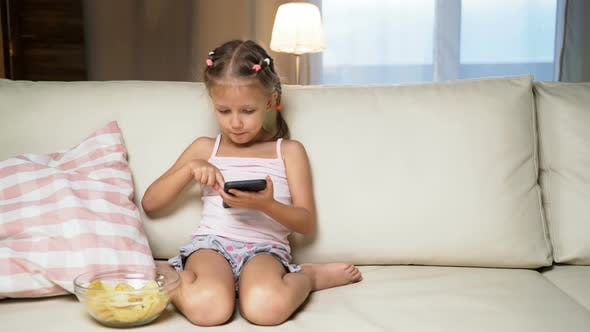 Cover Image for Little Girl Child Home On Sofa Playing On Smartphone