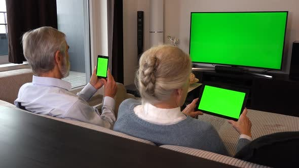 Thumbnail for Elderly Couple Sits in A Living Room, Watches TV With a Green Screen and Looks at Phone and Tablet