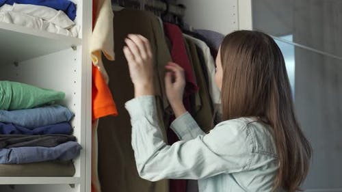 Young Attractive Woman Chooses Clothes in a Wardrobe at Home