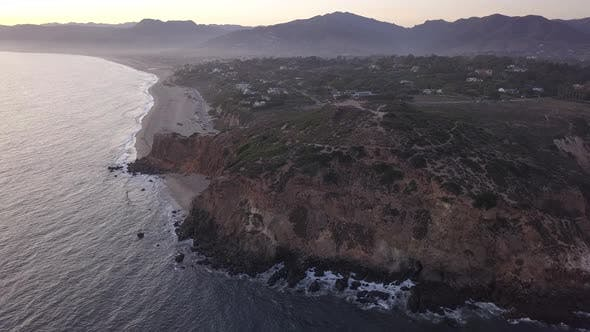 AERIAL: Flight Over Malibu, California View of Beach Shore Line Pacific Ocean at Sunset with