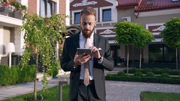 Thumbnail for Bearded Businessman Scrolling and Typing Text on His Tablet Standing
