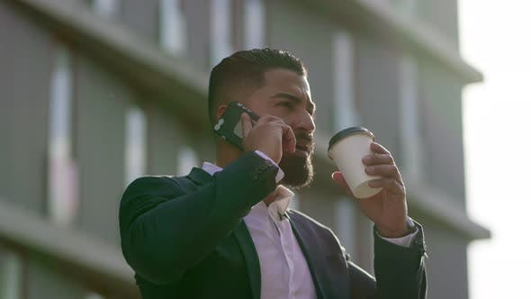Thumbnail for Man Drinking From Paper Cup and Talking By Smartphone