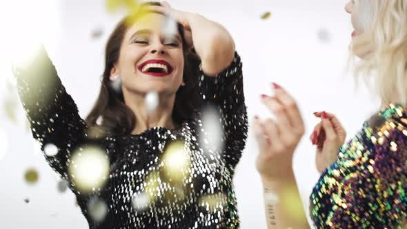 Thumbnail for Two women dancing under shower of confetti in studio shot