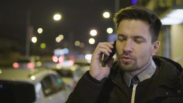 Thumbnail for A Young Handsome Man Talks on a Smartphone with a Smile in a Street in an Urban Area at Night
