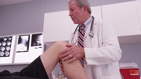 Thumbnail for Male caucasian patient having knee examined by mid aged doctor