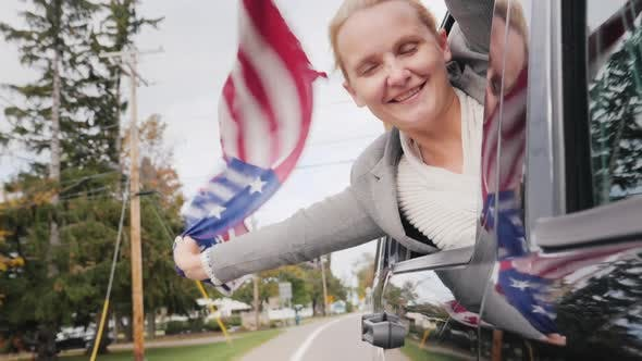 Thumbnail for Happy Middle-aged Woman with an American Flag. Looks Out the Window of a Moving Car. Slow Motion