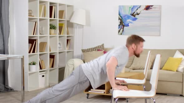 Thumbnail for Athletic Man Doing Push Ups on Two Chairs while Training at Home