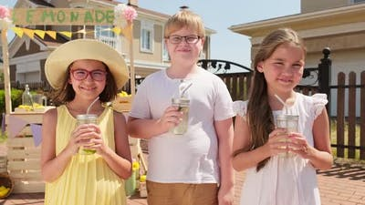 Kids Drinking Lemonade Outdoors In Summer