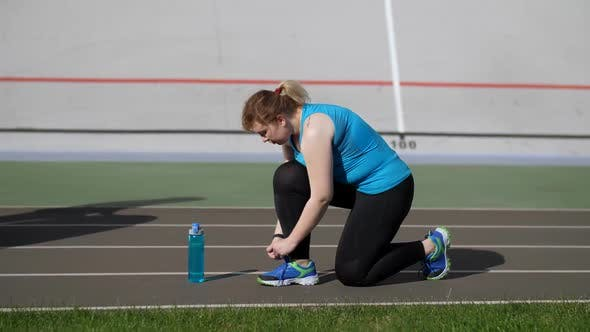 Thumbnail for Active Fat Woman Runner Tying Shoelaces on Stadium