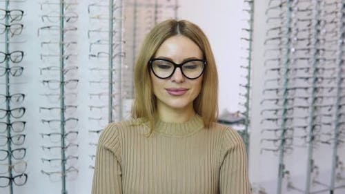 Attractive Young Caucasianblonde Woman Standing in Front of the Camera Wearing Transparent Glasses