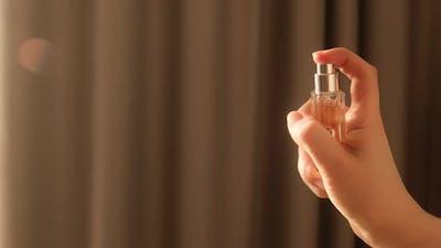 Hand spraying dust perfume, Slow motion. Applies perfume.