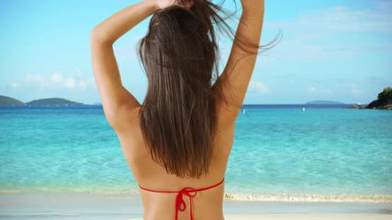 Thumbnail for A Hispanic girl looks away from the camera on the beach