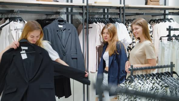 Woman Trying on Jacket While Shopping with Friends